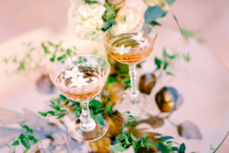 Pink florals, greenery, and drinks on a table