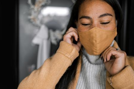 Person putting on orange mask