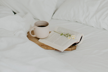 A bed with a book and a coffee cup