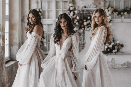 Three brides standing with long flowy dresses with blush undertones